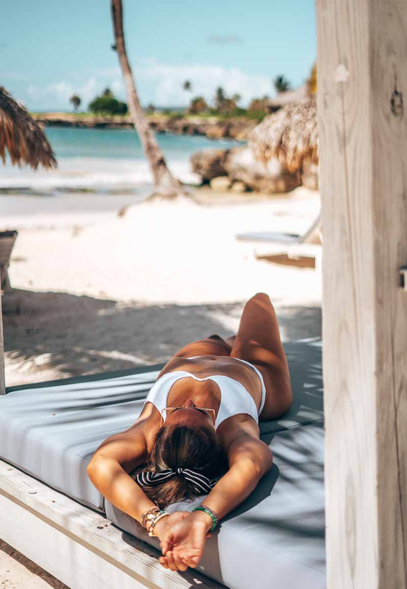 woman in white bikini relaxing in cabana