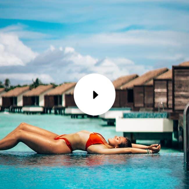 woman lying on pool edge overwater bungalow