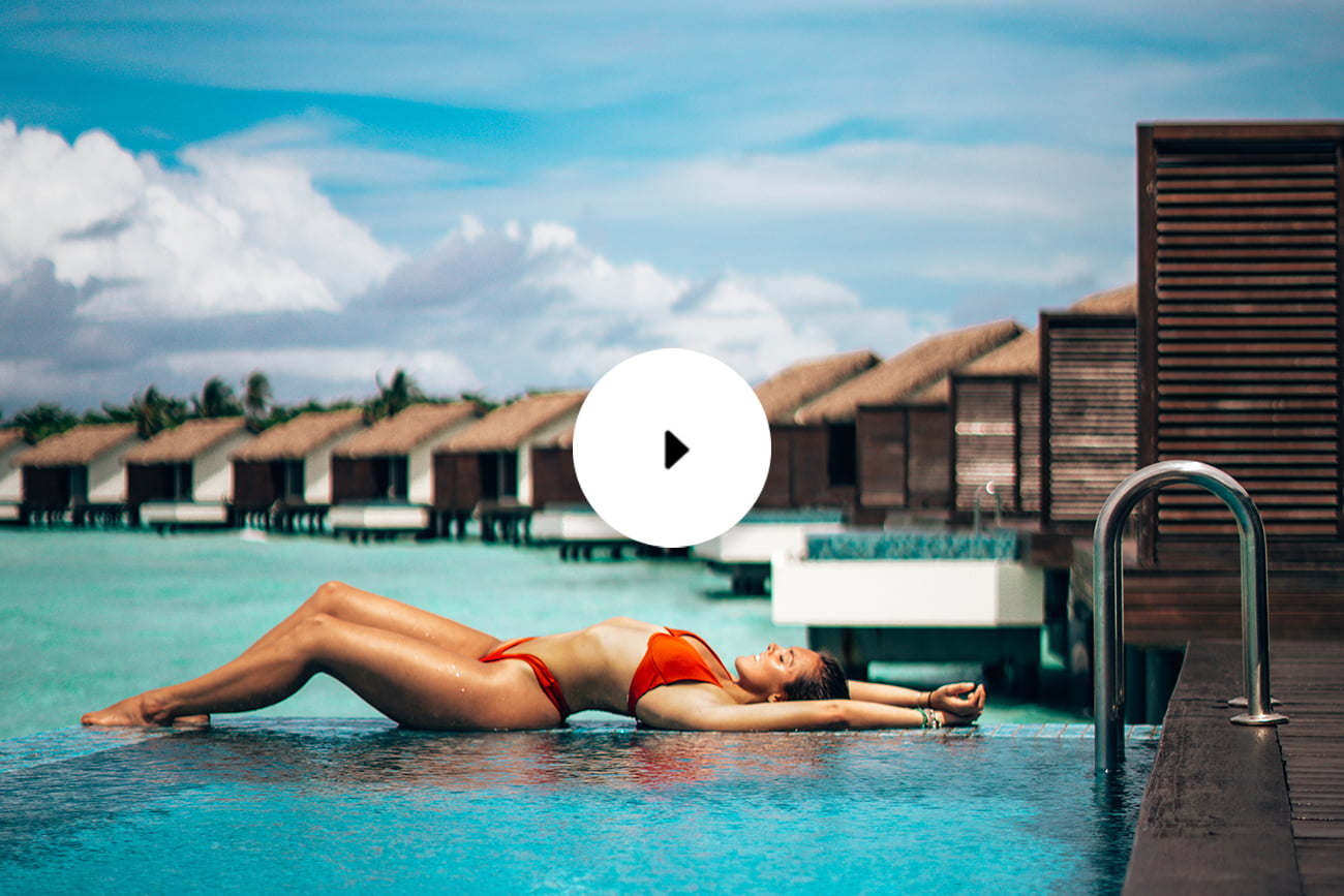 woman lying on pool edge overwater bungalow